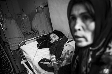 A woman holds the hand of another woman who lies on a hospital bed being treated after she attempted suicide following being forced to marry against were will. In the background a group of women weari...
