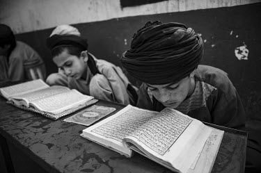 A class of boys study the Quran at the Islami Noor madrassa.