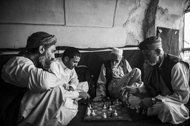 A group of men play a chess in a cafe.