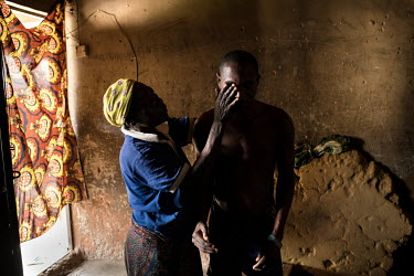 Joshua Aliyu (25) with his mother Laraba Alhaji. Joshua says his illness started six years ago with difficulty moving his hand. Stiffness and pain spread through his body. He also started to struggle...