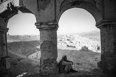A man sitting on the hill housing the Nader Shah tomb which overlooks the capital.