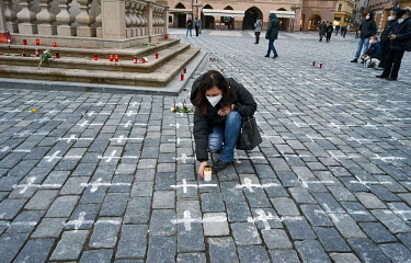 A woman lights a candle in the Old Town Square, where 25,000 crosses have been painted on the cobbles, one for each person who has died from COVID-19. The crosses were painted by the group a Million M...