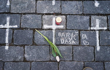 A tulip and a candle laid beside a cross painted on the cobbles in the Old Town Square. Beside the cross a relative of a woman who died from COVID-19 has written 'Grandmother Dasa' in tribute. The cro...