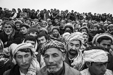 A crowd of excited male spectators watch a game of Buzkashi, Afghanistan's national sport. Literally translated as 'goat grabbing', it is played by two teams of men on horseback. They battle for contr...