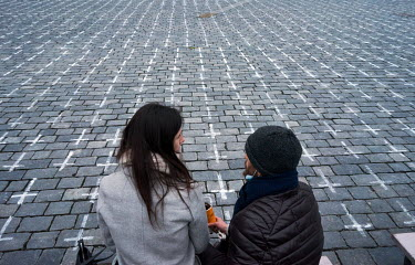 A couple sit among the 25,000 crosses painted on the cobbles in the Old Town Square, each cross a tribute to a person who has died from COVID-19. The crosses were painted by the group a Million Moment...
