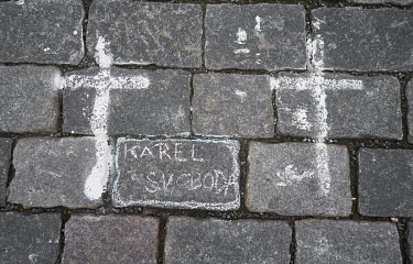 A cross painted on the cobbles in the Old Town Square where a relative has written 'Karel Svoboda' in tribute to a man who died from COVID-19. The crosses were painted by the group a Million Moments f...