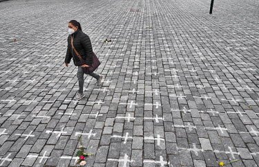 A woman walks through the Old Town Square, where 25,000 crosses have been painted on the cobbles, one for each person who has died from COVID-19. The crosses were painted by the group a Million Moment...