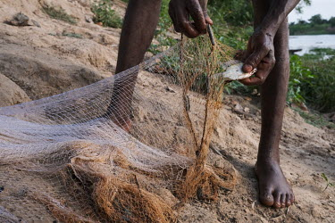 Moise Avihoue removing a meagre catch from his net along the Oueme River on the edge of the village of Dekanme. Dwindling fish stocks are one of many factors that accelerate pressure on forests, as pe...