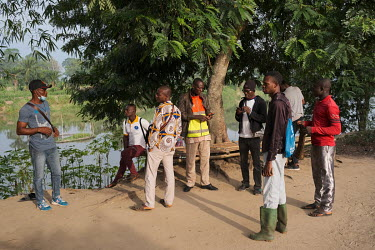 Local youth waiting in the village of Dekanme to board pirogues and cross the Oueme River to a small sacred forest grove on the opposite bank, where they will use Android tablets and a mobile app to c...