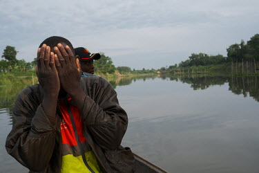 A man rubs his eyes as local youth cross the Oueme River to a small sacred forest grove on the opposite bank, where they will use Android tablets and a mobile app to conduct a biodiversity survey.  Wh...