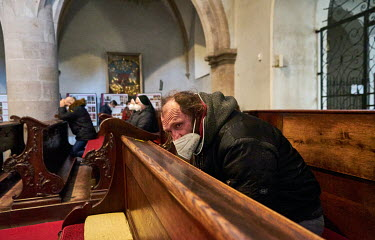 A homleless man praying on Palm Sunday in the Church of the Assumption of the Blessed Virgin Mary. Believers must be registered, due to COVID-19 lockdown restrictions, only 20 people are allowed at Ma...