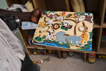 Beninese conservationist Yves Olatoundji showing a children's puzzle at a conservation education centre in the village of Gbineji along the Oueme River. Using a combination of methods including reinfo...