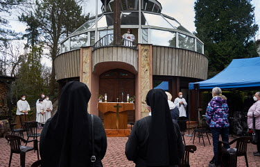 A clergyman rings the bell during a Maundy Thursday Mass conducted in a Meditation Garden.