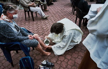 Catholic priest Pavel Petrasovsky washes the feet of believer during a Maundy Thursday Mass conducted in a Meditation Garden.