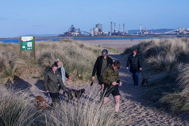 People walking dogs in the Teesmouth National Nature Reserve. In the background are is the closed-down Redcar Steelworks, shut due to the inability to compete with cheaper foreign production, primaril...