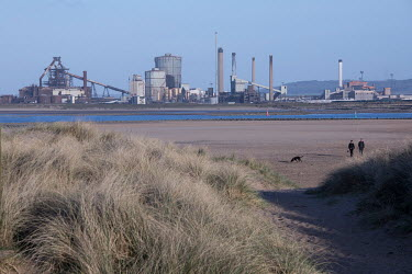 People walking dogs towards the Teesmouth National Nature Reserve. In the background are is the closed-down Redcar Steelworks, shut due to the inability to compete with cheaper foreign production, pri...