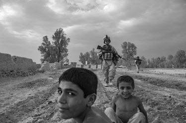 A soldier taking part in a US marine security patrol smiles while passing two boys playing on the ground.