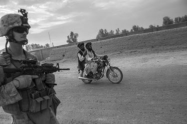 Two men on a motorcycle pass a US marine conducting a patrol in Helmand Province.