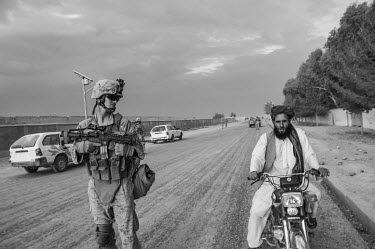 A US Marine conducting a patrol looks at a man on a passing motorcycle in Helmand Province.