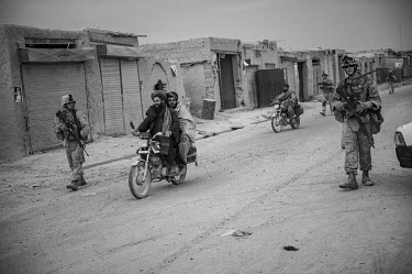 Men riding motorcycles pass a group of US Marines conducting a patrol.