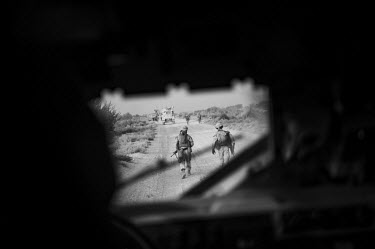 A group of US Marines conducting a patrol are seen through the window of a US military vehicle.