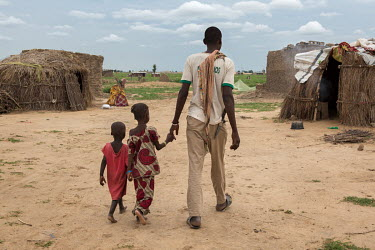 Ibrahim Jiddern with two of his children walk through through an IDP camp where he has fled with his family who are among thousands struggling to exist in various camps after fleeing their homes due t...
