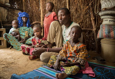 Ibrahim Jiddern with his family sit in a wood and grass thatch shelter in an IDP camp where they fled from their home due to the actions of Boko Haram. L-R Nana Mohammed (22) Oukurum Ibrahim (1) twinn...
