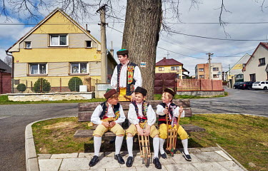 Boys dressed in Chod folklore costumes, L-R: Vasek (11), Simon (11), Matyas (8) and Vita (15), relaxing on a bench as they make noise with wooden rattles as a substitute for the ringing of church bell...