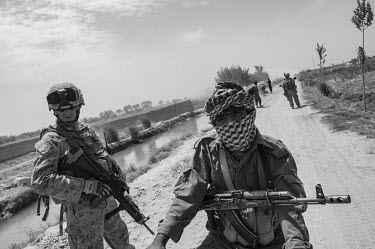 US marines and the ANP (Afghan National Police) conduct a security patrol.