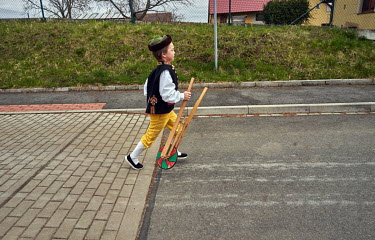 An eight year old Matyas, dressed in Chod folklore costume, walks through the Mrakov village making noise with a wooden rattle, a substitute for the ringing of church bells.��