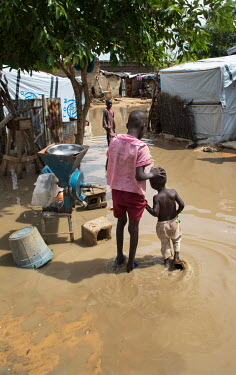 Two boys walk through food flood water in the Shuwari camp, home for some of the thousands of IDPs that are struggling to exist after fleeing from their homes due to the actions of Boko Haram.