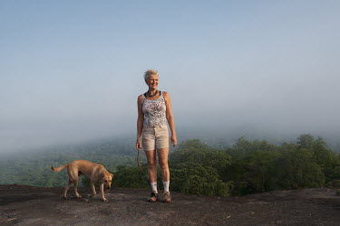 Karin Ostertag and one of her dogs on an outcrop above the Tobe protected forest. Some 350 hectares in area, the forest had been severely degraded by agriculture. Over the last 35 years it has been re...