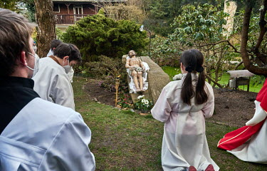 Altar boys and girls of the Church of the Assumption of the Blessed Virgin Mary meditate at the Lord's Tomb in a Meditation Garden.