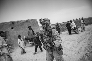 A US marine participates in a security patrol passing villagers.