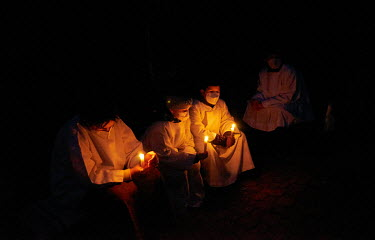 Altar boys and an altar girl holding lighted candles during an Easter�Vigil on the night of�Holy Saturday in a meditation garden.