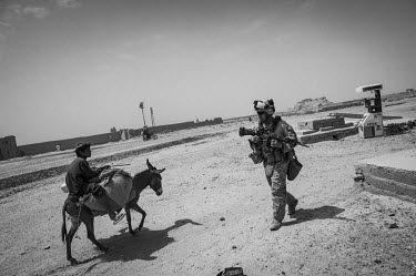 A US Marine passesa boy riding a donkey while conducting a security patrol.