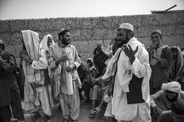 A group of shopkeepers pray after holding a Shura (meeting), guarded by US Marines and Afghan National Army soldiers. The Shura had been convened to discuss the reopening of the Safar Bazaar, in Helma...