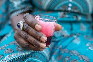 A woman holds a glass of hot hibiscus tea. The infusion, known as bissap, is one of the country's most popular drinks.