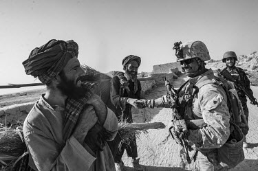 A US Marine on security patrol interacts with two Afghan men.