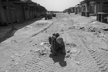 A US Marine checks for IEDs during a patrol through the Safar Bazaar, after improvised explosive devices were reported to have been planted there by the Taliban.