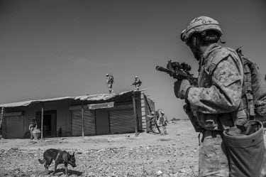 US Marines on patrol through the Safar Bazaar where improvised explosive devices were reported to have been planted by the Taliban.