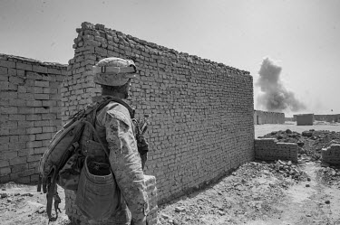 A US Marine looks at smoke rising from a controlled detonation of an IED discovered by US Marines on patrol in the Safar Bazar.