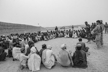 Shopkeepers hold a shura (meeting), guarded by US marines and the ANA (Afghan National Army), to discuss the reopening of Safar bazaar. The bazaar had been closed because of IEDs (improvised explosive...