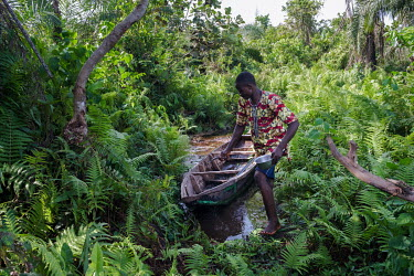 Desire Segla mooring a pirogue in a wetland conservation area established by the NGO GRABE Benin (Groupe de Recherche et d'Action pour le Bien-Etre/ Research and Action Group for Well-Being) in the vi...