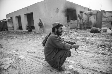 A shopkeeper sits outside a shop where a US Marine is standing guard. The bazaar had been damaged due to fighting between US forces and the Taliban.