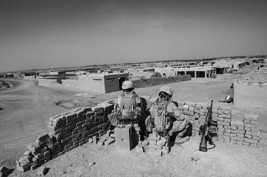 Two US Marines guard an intersection in Helmand Province.