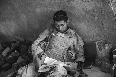 A US marine reads a book as he takes a rest after a patrol.