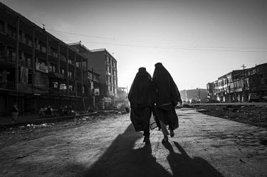 Burqa-clad pedestrians walk along a street. The war-torn country, beset by a decade-long Taliban insurgency and rampant corruption, is one of the world's poorest, with more than a third of the populat...