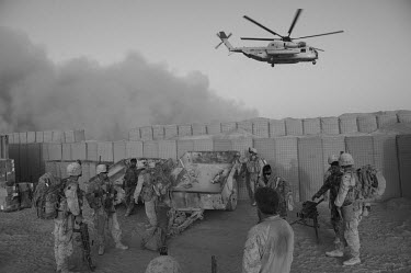 US marines and ANA (Afghan National Army) soldiers prepare to leave the base for a joint patrol as behind them a helicopter prepares to land. On many patrols, the two military forces work together.