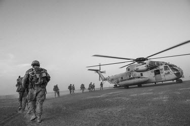US marines walk towards a helicopter to begin a patrol.